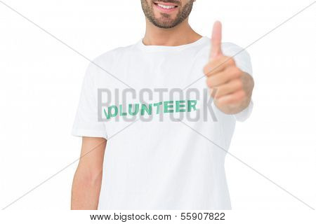 Close-up of a happy male volunteer gesturing thumbs up over white background