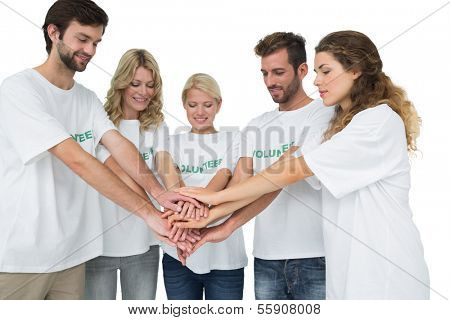 Group of young volunteers with hands together over white background