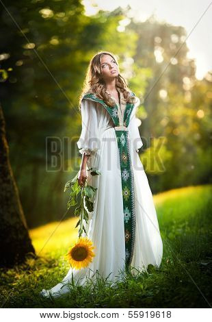 Young woman wearing a long white dress holding a sunflower outdoor shot. Portrait of beautiful girl