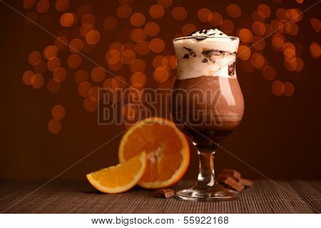 Tasty dessert with chocolate, cream and orange sauce, on table, on lights background