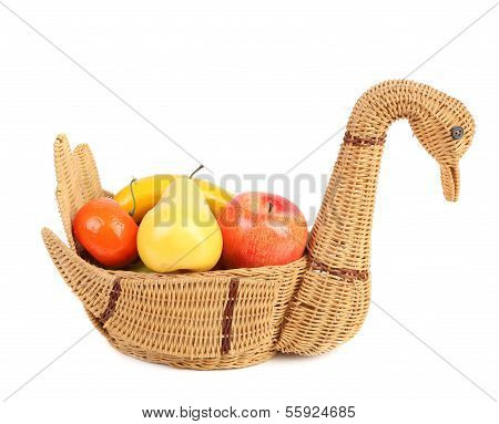 Artificial fruits in wicker basket isolated