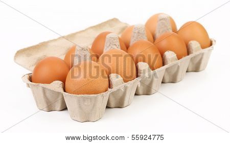 Ten brown eggs in box