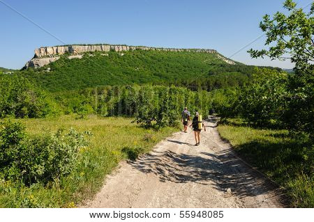 Two people hiking with backpacks at the road in central Crimea, Ukraine