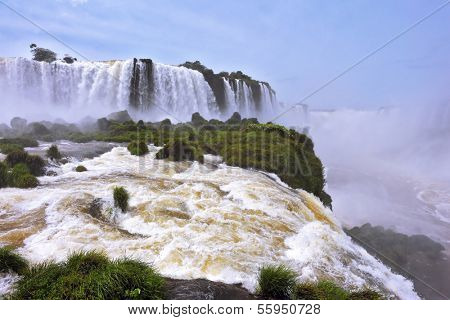 The grand Iguazu Falls on the Brazilian side. Multi-tiered cascades of water roar of lush jungle. Over boiling water swirls fine mist
