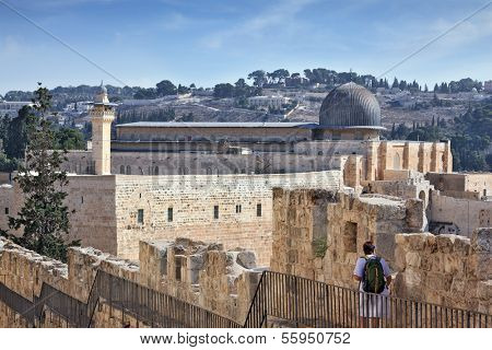Along the walls of Jerusalem, is a brooding woman- pilgrim with a backpack. In the distance you can see the gray dome of the Al-Aqsa Mosque and the Muslim minaret