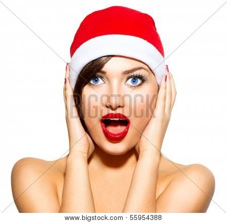 New Year Woman. Beauty Christmas Model Girl in Santa Hat isolated on White Background. Funny Laughing Surprised Woman Portrait. Open Mouth. Emotions. Red Lips and Manicure. Beautiful Holiday Makeup.