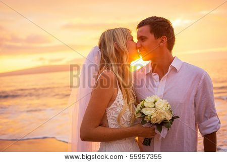 Just married couple kissing on tropical beach at sunset, Hawaii Beach Wedding
