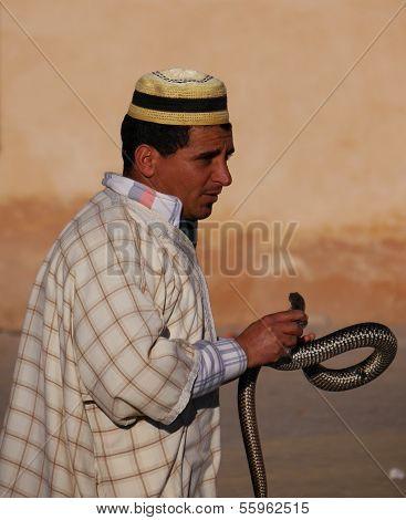 Moroccan snake charmer in hat holding snake