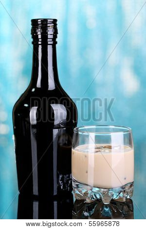 Baileys liqueur in bottle and glass on blue background