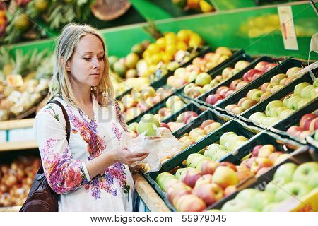 Woman choosing bio food fruit apple in vegetable supermarket during shopping