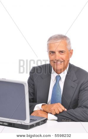 Middle Aged Businessman Seated Looking Over Top Of Laptop