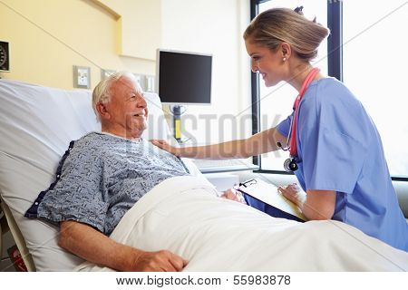 Nurse Talking To Senior Male Patient In Hospital Room