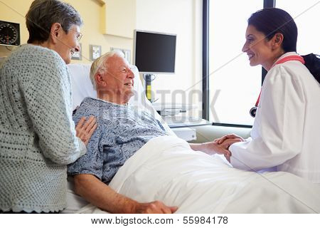 Female Doctor Talking To Senior Couple In Hospital Room