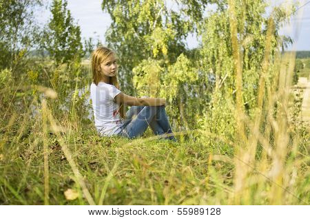 young girl sitting in the grass