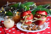 Stuffed Christmas apples with nuts and raisins on table on wooden background
