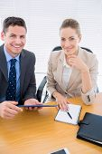 stock photo of sm  - Portrait of a smartly dressed young man and woman in a business meeting at office desk - JPG