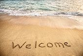 foto of sunny beach  - Welcome word on the sand beach near the ocean - JPG