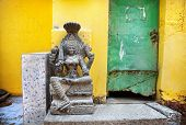 pic of tamil  - Stone Goddess near grunge yellow wall and green door in Mamallapuram cave Tamil Nadu India - JPG