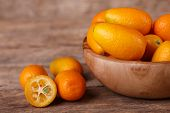 picture of kumquat  - Fresh ripe orange kumquats on wooden background - JPG