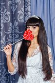 picture of tick tock  - Attractive young brunette girl hiding behind big lollipop - JPG