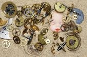 stock photo of oddities  - Detail of the clockwork mechanism on the sand and puppy head - JPG