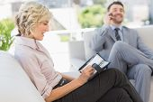 Businessman on call and secretary with diary sitting on sofa at home