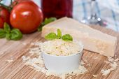 stock photo of grating  - Heap of fresh grated Parmesan Cheese on wooden background