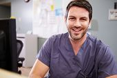 stock photo of nurse  - Portrait Of Male Nurse Working At Nurses Station - JPG