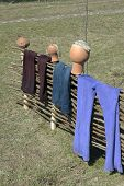 picture of wet pants  - Wet pants after laundry hanging on fence and clay jugs - JPG