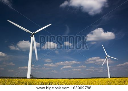 Low perspective view of two Wind Turbines in Canola Field