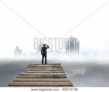 Businessman Gazing At City With Cloudy Under