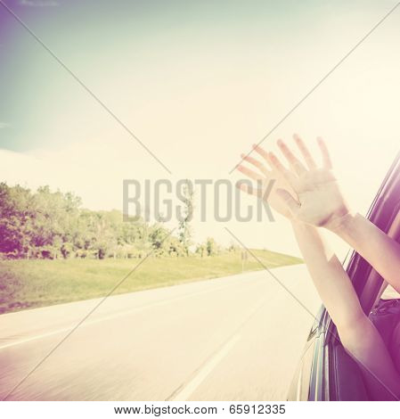 Child putting their hands out of the car window