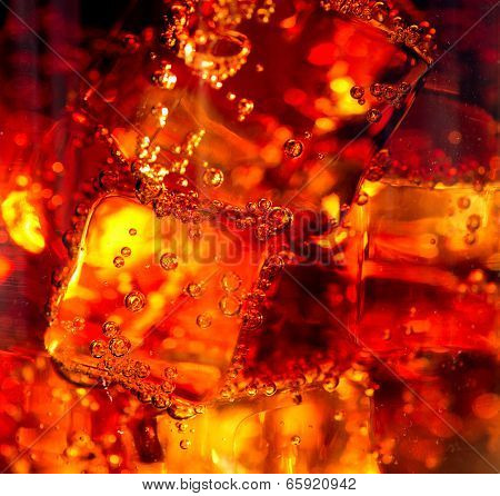 Cola background. Cola with Ice and bubbles in glass closeup. Food background