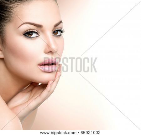 Beautiful Young Woman with Clean Fresh Skin close up isolated on white. Beauty Portrait. Spa Woman Smiling and touching her skin. Perfect Fresh Skin. Pure Beauty Model. Youth and Skin Care Concept