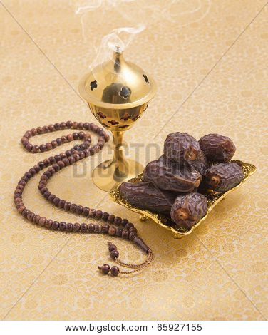 An oudh burner, prayer beads and dates
