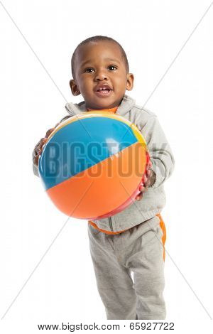1 year old African American baby boy standing holding beach ball on isolated background