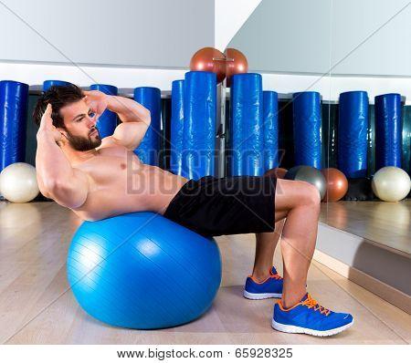 Fitball abdominal crunch Swiss ball man at fitness gym