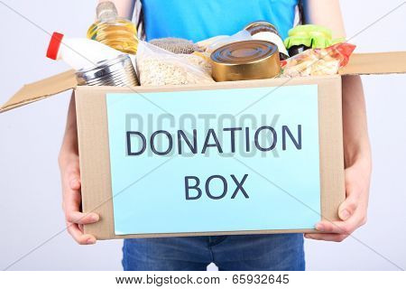 Volunteer with donation box with foodstuffs on grey background