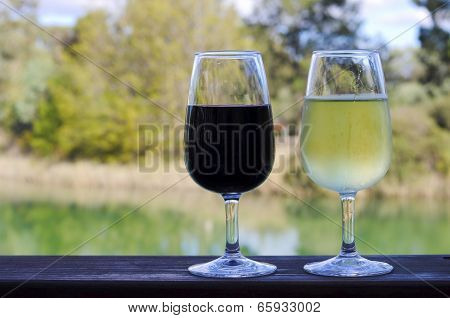 Two Glasses Of Wine, White And Red, On Wooden Rail With Country Rural Scene In Background.
