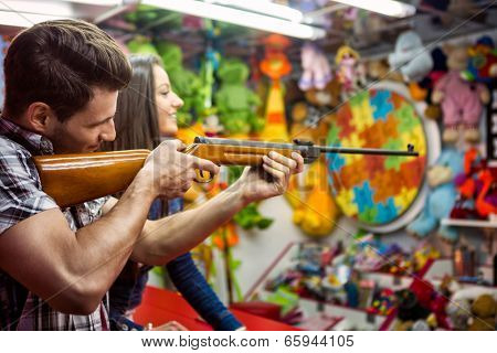 couple playing shooting games while visiting an amusement park, young man holding gun and shooting