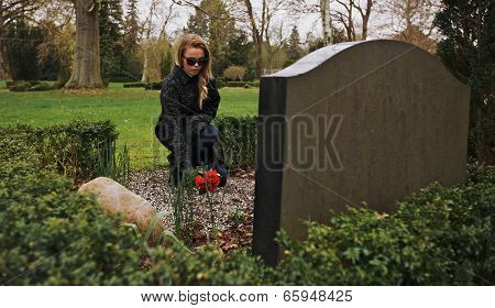 Young Woman Grieving At Graveyard
