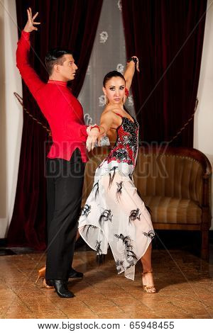 Young dance couple preforming latin show dance in beautiful ancient ballroom