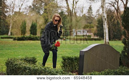 Woman At The Cemetery Paying Respects With Fresh Flowers