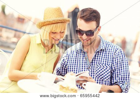 A picture of a young couple reading a guide in an outdoor cafe