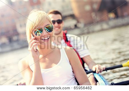 A picture of a young woman talking on the phone in a canoe
