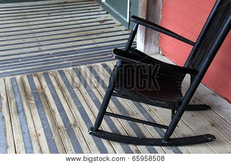 Old black rocking chair on out door rug