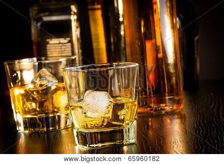 Two Glasses Of Whiskey In Front Of Bottles