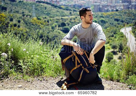 Young hiker resting on a halt on a mountain trail and looking away