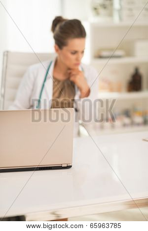 Closeup On Laptop And Thoughtful Medical Doctor Woman In Backgro