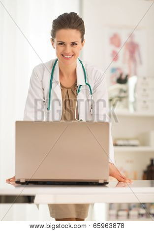 Portrait Of Happy Medical Doctor Woman With Laptop In Office